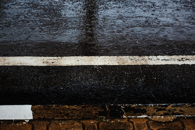 Percorso del piede bagnato durante la caduta di pioggia dura di notte, messa a fuoco selettiva. sfondo della stagione delle piogge.