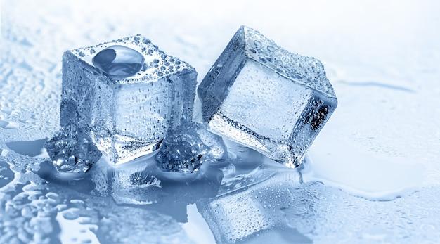 Cubetti di ghiaccio bagnati con pezzi di ghiaccio tritato e goccioline su sfondo blu