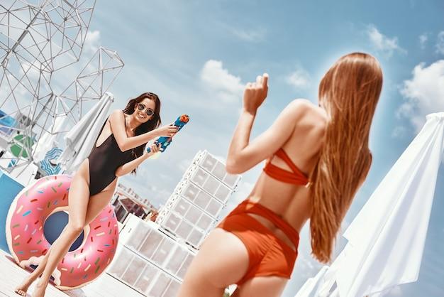 Ragazze sexy bagnate e selvagge che si divertono alla festa in piscina sul tetto rooftop