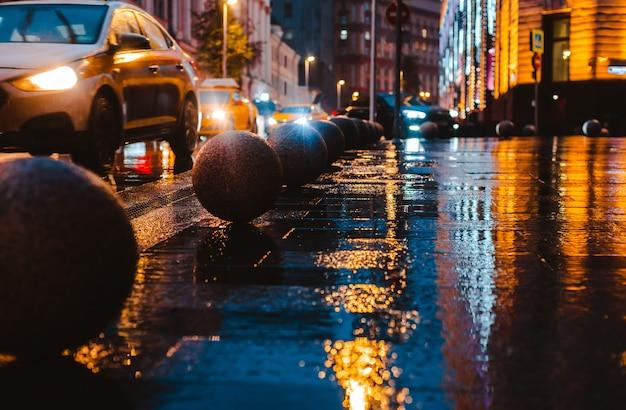 Automobile del marciapiede delle pozze delle luci variopinte luminose di riflessione del bokeh della pioggia della via della città di notte bagnata