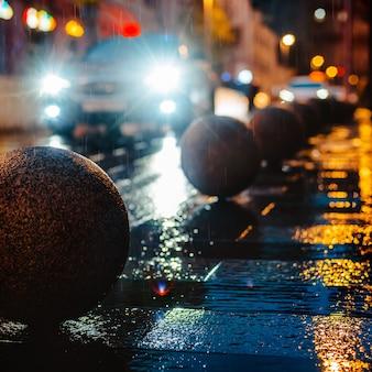 Automobile del marciapiede delle pozze delle luci variopinte luminose di riflessione di bokeh della pioggia della via della città di notte bagnata