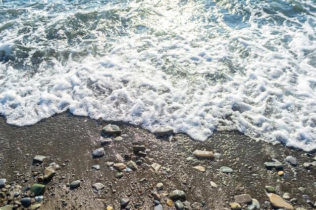 Sabbia bagnata, ciottoli e schiuma di mare in spiaggia. sfondo estivo