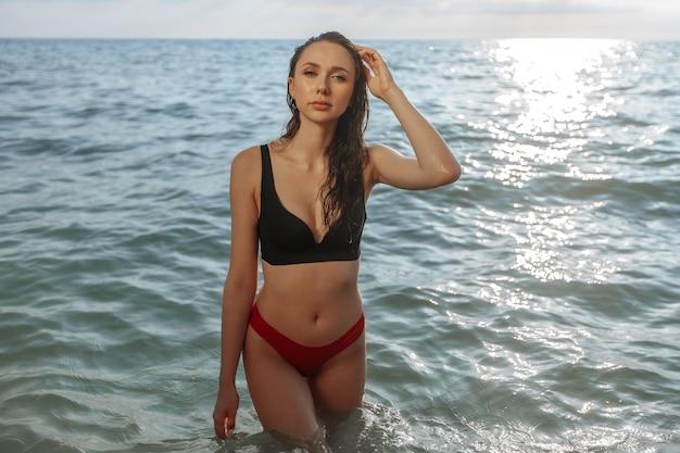 Ragazza sexy bagnata in costume da bagno esce dal mare