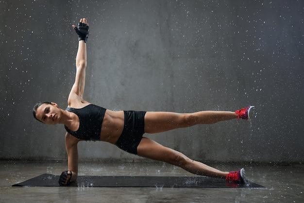 Donna bagnata che pratica esercizio laterale della plancia