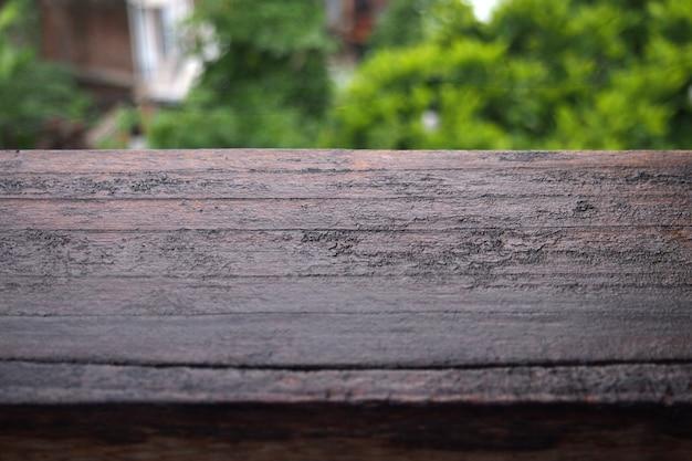 Piano d'appoggio di legno bagnato davanti agli alberi nel giardino