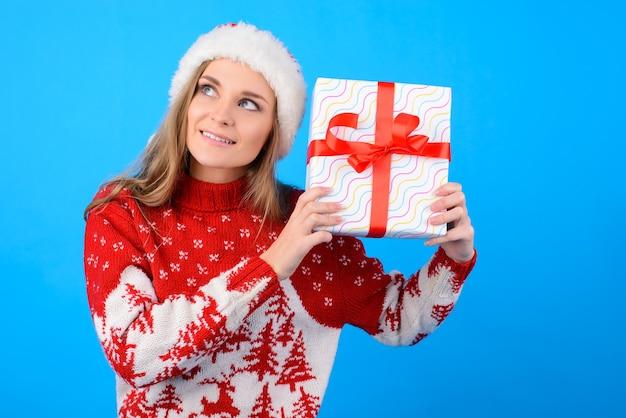Cosa può esserci? close up ritratto di eccitata gioiosa donna felice con una presente casella, isolata su sfondo blu