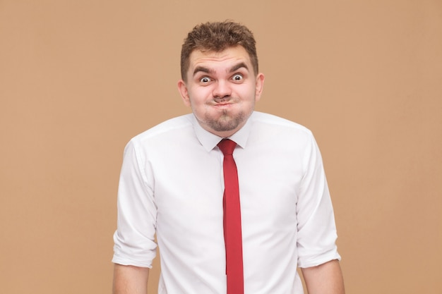 Che cosa? uomo divertente pazzo con un grande occhio che guarda l'obbiettivo. concetto di uomini d'affari, emozioni e sentimenti buoni e cattivi. studio girato, isolato su sfondo marrone chiaro
