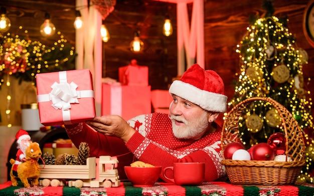 Che scatola carina composizione di natale. pronto per la festa di capodanno. l'uomo barbuto mangia i biscotti. atmosfera da vacanza invernale. celebrazione della festa di natale. il nonno beve il latte. babbo natale cena. per babbo natale.