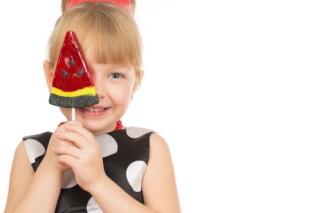 Che carino. ritratto di una dolce bambina che ride nascondendo il viso dietro un grande lecca-lecca a forma di fetta di anguria