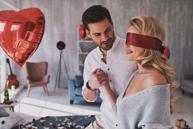Cosa aspettarsi? bella giovane donna che cammina con gli occhi bendati attraverso la camera da letto con il suo ragazzo mentre trascorre del tempo a casa