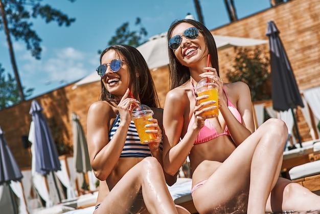 Che bel fine settimana due giovani donne giocose e belle in costume da bagno che sorridono e bevono
