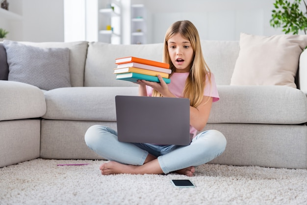 Quello che mi serve leggere tutti i libri. la ragazzina frustrata si siede sul pavimento e studia a distanza con il computer portatile che comunica con il tutor online ha impressionato i materiali di conoscenza del compito dell'esame in casa al chiuso