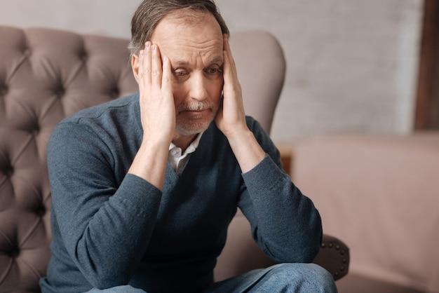 Che cosa è successo. chiuda in su dell'uomo anziano frustrato che si siede sul divano e che tocca le sue tempie con le mani.