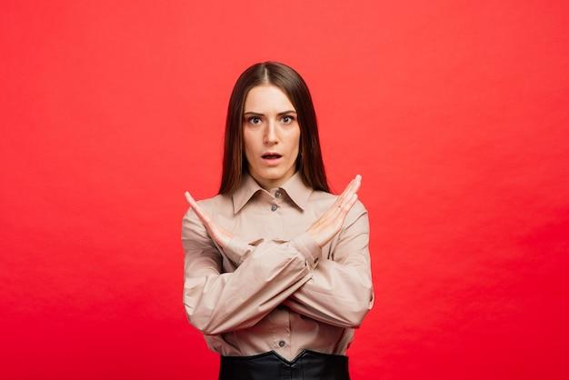 Che cos'è. il ritratto femminile isolato sulla parete rossa. la giovane donna arrabbiata e spaventata emotiva che guarda l'obbiettivo. le emozioni umane, il concetto di espressione facciale.