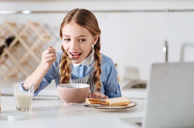 Cosa c'è dopo. vivace e allegra graziosa bambina che si gode un nuovo episodio del suo cartone animato preferito mentre mangia il suo pasto mattutino composto da cereali e panini al cioccolato