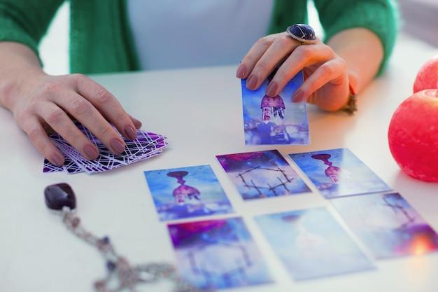 Qual è il significato. carta dei tarocchi nelle mani degli indovini mentre è pronta per essere aperta