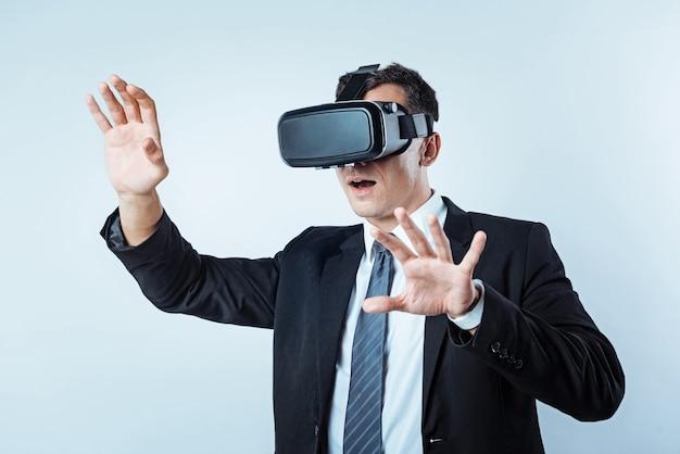 Che cos'è. inquadratura dalla vita di un imprenditore emotivo che tiene la bocca spalancata mentre fa nuove esperienze e indossa un visore vr.