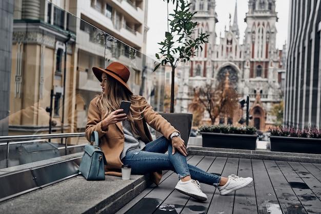 Cosa c'è? attraente giovane donna con cappello e cappotto che si guarda alle spalle mentre è seduta all'aperto con la chiesa sullo sfondo