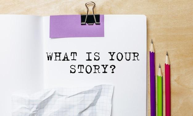 Qual è la tua storia testo scritto su un foglio con le matite sulla scrivania in ufficio