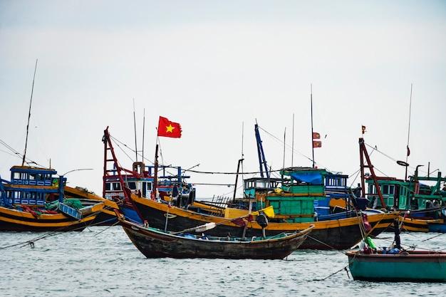 Quante barche su questa spiaggia, mui ne, vietnam. in una giornata di sole nel sud del vietnam, una folla di barche di pescatori di ritorno dal piscatory in attesa di entrare nel molo. paesaggio