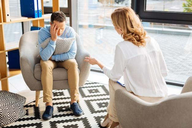 Cosa fare. bel uomo triste infelice che tiene un cuscino e ascolta il suo medico mentre cerca di far fronte alla depressione