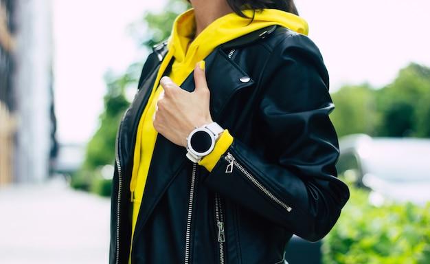 Che bel design! look da giovane donna, che consiste in giacca di pelle, felpa con cappuccio gialla e il suo nuovo smartwatch ben progettato.