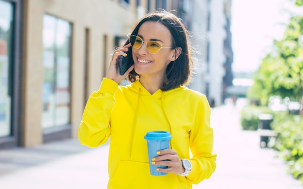 Cosa c'è di nuovo? un primo piano di una bella ragazza sorridente con gli occhiali gialli per strada, con una tazza termica blu e uno smartwatch bianco in mano, che parla al suo telefono moderno.