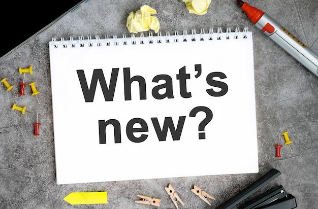 Novità testo su un taccuino bianco con puntine, pennarello e cucitrice su un tavolo di cemento