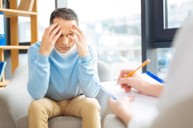 Cosa fare. uomo triste depresso triste che si siede di fronte al suo medico e buca la testa senza sapere cosa fare