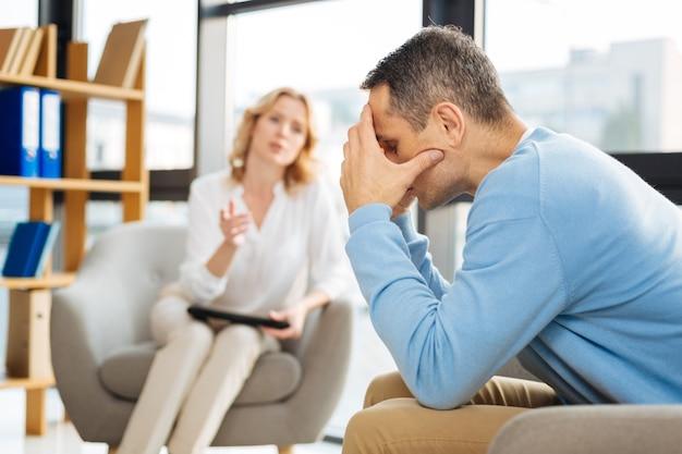 Cosa dovrei fare. cupo depresso uomo infelice seduto di fronte al suo terapista e coprendosi il viso pur avendo problemi personali