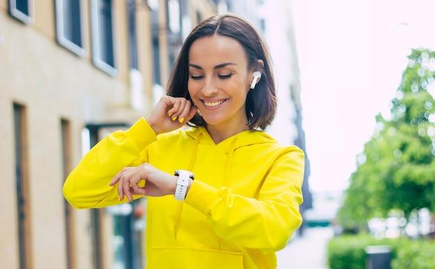 Che ore sono adesso? un primo piano di una bella ragazza sorridente con una felpa gialla con unghie gialle, rimboccandosi i capelli, guardando il tempo sul suo smartwatch.