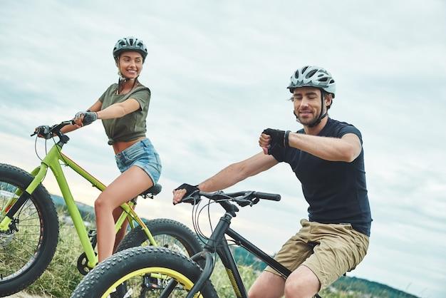Che ore sono le giovani coppie che vanno in bicicletta su fatbike e con i caschi da vicino