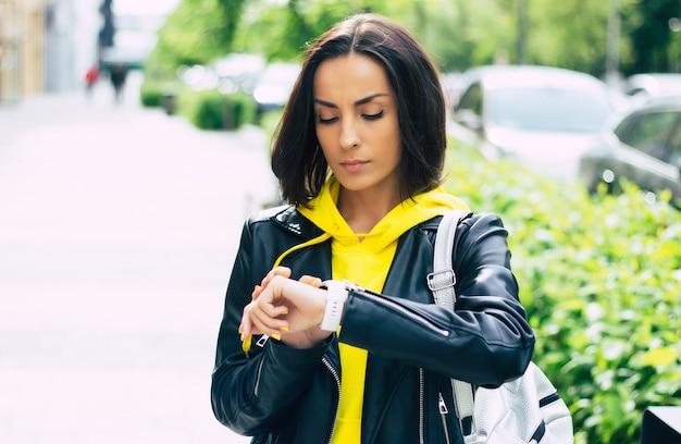 Che ore sono? giovane donna, vestita con giacca di pelle e felpa con cappuccio gialla, controlla che ore sono con il suo nuovo smartwatch moderno.