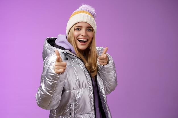 Ehi amico. ragazza bionda sveglia sorridente felice eccitata amichevole che controlla fuori la scelta piacevole dell'attrezzatura fresca della ragazza che indica la macchina fotografica delle pistole del dito che sta sorridendo divertito in giacca invernale.