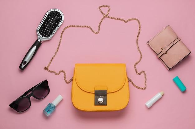 Cosa c'è nella borsa scarpe accessori donna su sfondo rosa pastello concetto di bellezza e moda