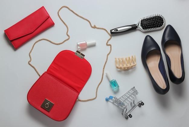Che cosa è nella borsa delle donne borsa in pelle rossa con scarpe da donna accessori cosmetici prodotti tacco alto su sfondo bianco