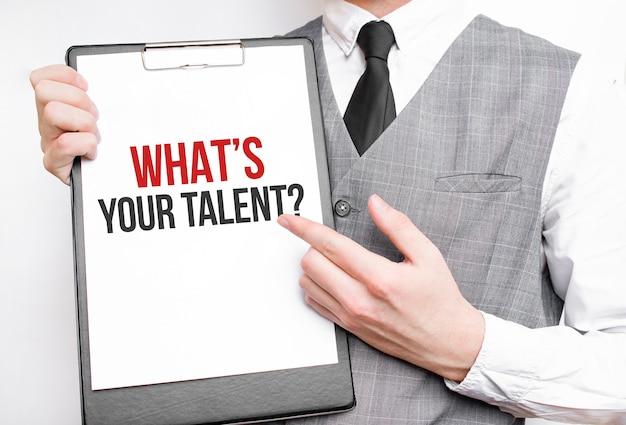 Qual è il tuo talento iscrizione su un taccuino nelle mani di un uomo d'affari su uno sfondo grigio