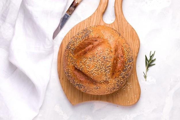 Pane di grano con il primo piano di semi di papavero e sesamo su una tavola di legno su uno spazio bianco.