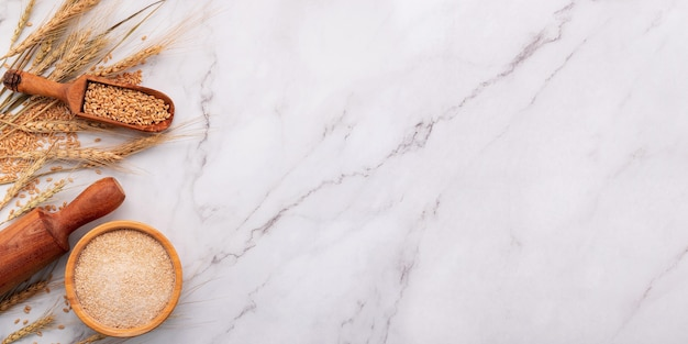 Spighe di grano e chicchi di grano allestiti su sfondo marmo. vista dall'alto e copia spazio