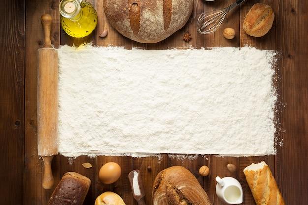 Farina di frumento e ingredienti da forno sul fondo della tavola in legno