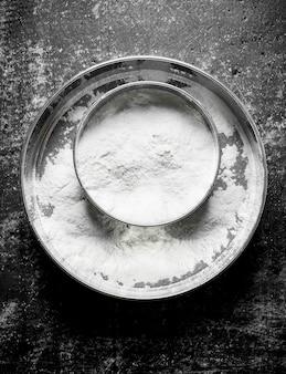 Setaccio di farina di frumento sul tavolo rustico.
