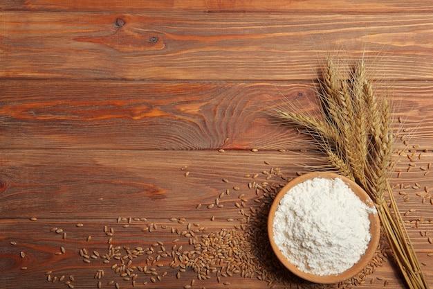 Farina di frumento e spighette di frumento su fondo chiaro