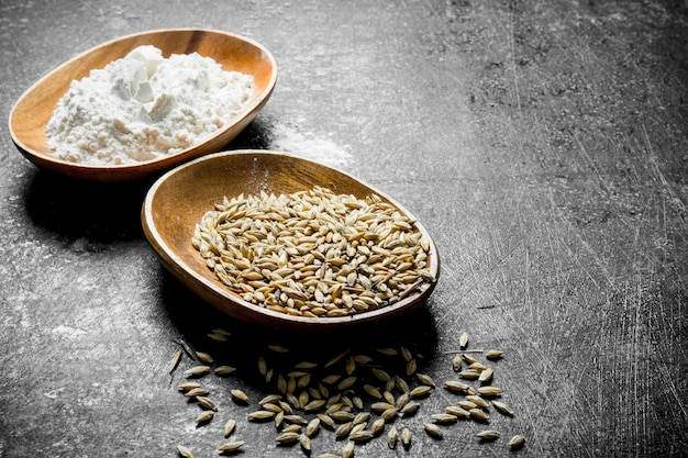 Chicco di grano e farina in ciotole sul tavolo rustico scuro.