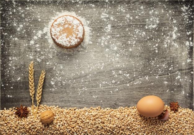 Chicchi di grano e ingredienti da forno su sfondo di legno, vista dall'alto