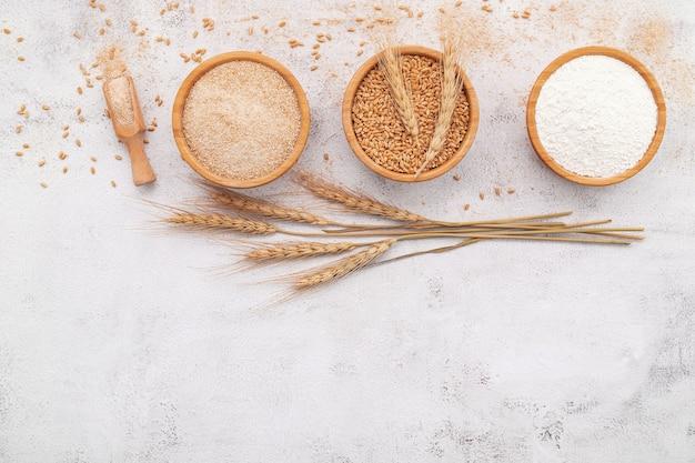 Chicchi di frumento, farina di frumento integrale e farina di frumento bianca in una ciotola di legno allestita su fondo di cemento bianco.