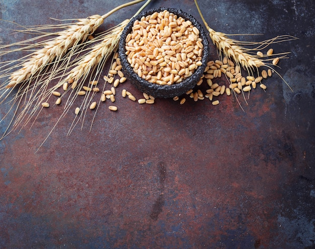 Chicchi di grano e spighette su sfondo arrugginito
