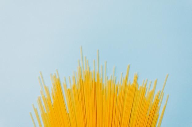 Spaghetti di pasta di grano su sfondo blu. vista dall'alto