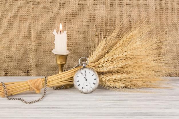 Grano e orologio da tasca sulla tavola di legno