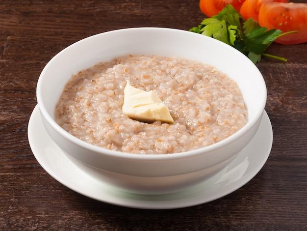 Porridge di grano con un pezzo di burro in un piatto bianco