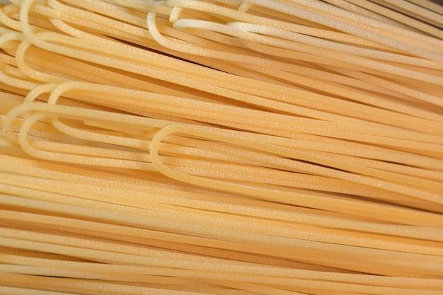 Spaghetti di grano crudo lungo giallo chiaro si trovano in primo piano cucina